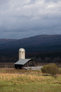 Magic light hits a barn and silo with mountains in teh background