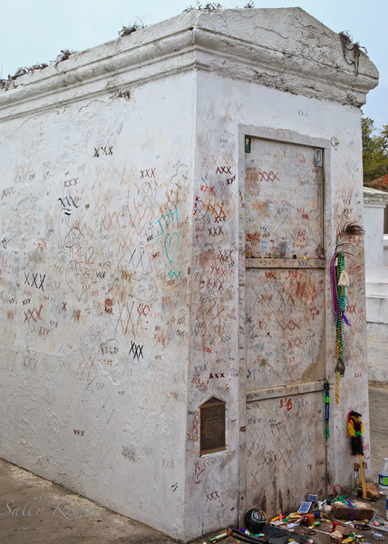 "The reputed tomb of Marie Laveau, famed ""Voodoo Queen"".  Marked with ""XXX"" in hopes of receiving favors covers the tomb and at the base are offerings from followers."