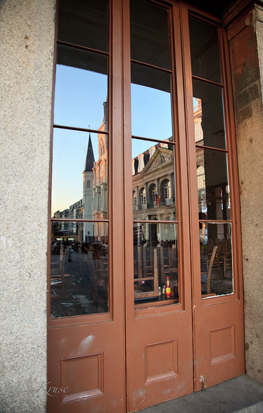 Reflection of the St Louis Cathedral in the windows of the Cafe Pontalba on St Peter Street in New Orleans.