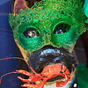 A paper mache dog eating a lobster and wearing a Mardi Gras mask in a shop window in New Orleans.