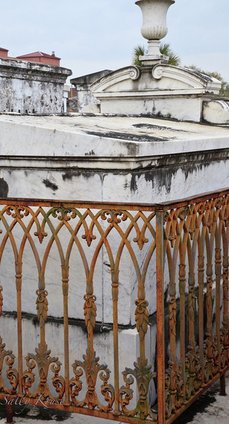 An elaborate but rusty wrought iron fence encircling a tomb in the St. Louis Cemetery #1, New Orleans.
