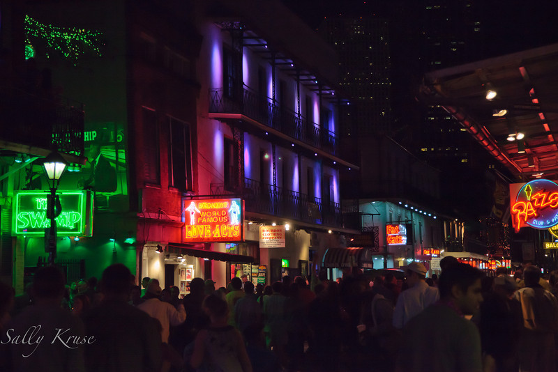 Bourbon Street in the French Quarter in New Orleans.  Lights from the clubs and high rises barely illuminating the crowd.
