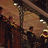 A group of fun loving guys tossing beads from a balcony to the crowd below on Bourbon Street in New Orleans.