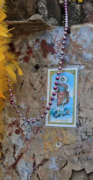 On the side of a tomb of a voodoo practitioner is the holy card of Saint Expedite, the patron of those who wish for rapid solutions to problems.  After he grants your request you must give him a gift of flowers or pound cake.  There was a lot of pound cake at the foot of this tomb.