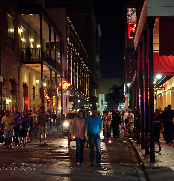 Pedestrians walking in the middle of a French Quarter side street in New Orleans.