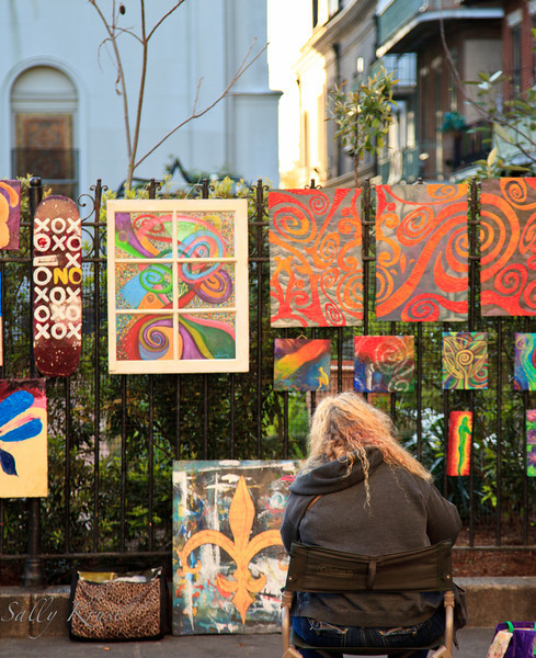 An artist selling her work which hangs from the wrought iron fence on the rear side of St Louis Cathedral in New Orleans