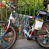 A bicycle decorated with beads leaning against the fence at the French Market, New Orleans.