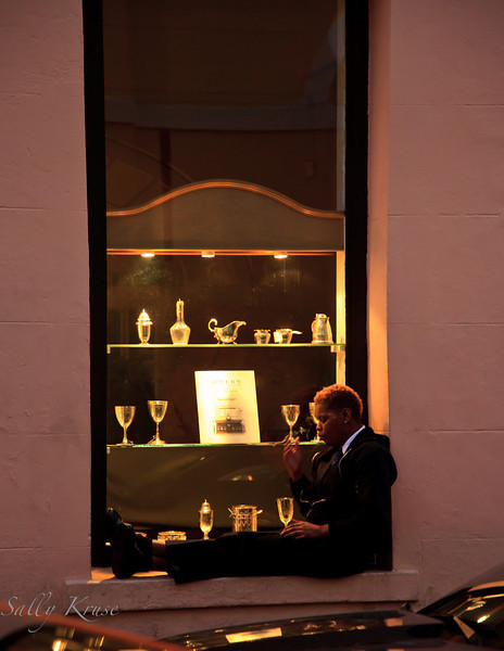 Taking a break from his shift, a waiter relaxes on a window ledge in New Orleans.
