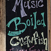 A sign advertising music and boiled crawfish in the storefront of an eatery in the Marigny/Bywater district, New Orleans.