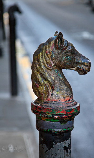 An old horse head hitching post with glitter and peeling paint located in the French Quarter, New Orleans.