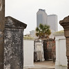 Old and decaying tombs in the St. Louis Cemetery #1 in New Orleans, contrasting with the modern city buildings in the background.