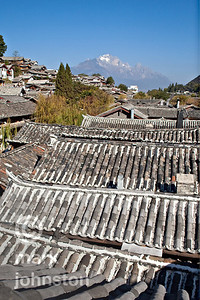 The rooftops of Lijiang, and the dominating presence of Yulong Snow Mountain in the distance.  Lijiang, in Yunnan Province, southwestern China, is a designated UNESCO World Heritage site.  These tile-roofed buildings are clustered around a three-branched river which runs through the town.
