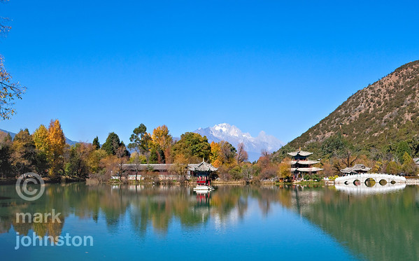 Northeast of the ancient town of Lijiang in Yunnan Province, China, within an area called the Jade Spring Park, lies the Black Dragon Pool.  On the horizon lies Yulong Snowy Mountain, whose highest peak Shanzidou reaches 5,596 meters. This scene is widely considered as one of China's finest views.  In the center of the lake is the tiny Yiwen Pavillion, and farther back to its right is the Deyue Pavilion [Moon-Embracing Pavilion].