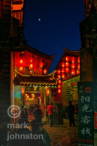 A crescent moon flies among the eves in the lantern-lit streets of Lijiang, Hunnan Province, China.  Lijiang is a UNESCO World Heritage site because of its well-preserved traditional Chinese houses, spectacular setting, and unique ethnic heritage.