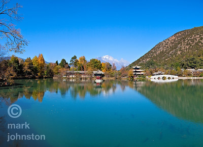 Northeast of the ancient town of Lijiang in Yunnan Province, China, lies the Black Dragon Pool, the surrounding area is called the Jade Spring park.  Beyond lies Yulong Snowy Mountain, whose highest peak Shanzidou reaches 5,596 meters.  This view is widely considered as one of China's finest.  In the center of the lake is the tiny Yiwen Pavillion, and farther back to its right is the Deyue Pavilion [Moon-Embracing Pavilion].