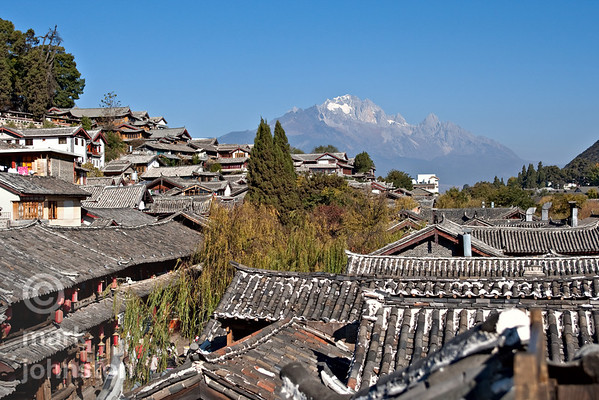 The well-preserved traditional tile-roofed houses in the city of Lijiang, Yunnan Province, China, lie beneath the rugged profile of Yulong Snowy Mountain, which reaches a height of 5,596 meters.