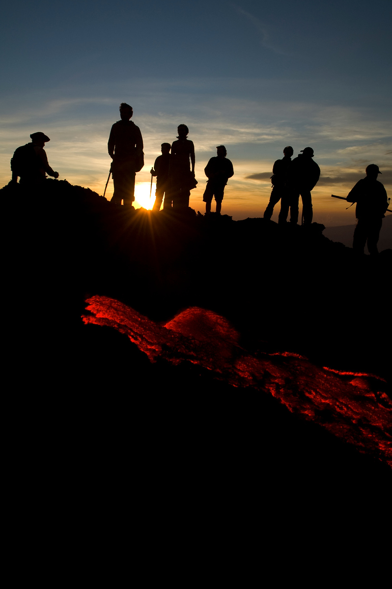 Pacaya Volcano Guatemala Adjustments: Increased the saturation of the lava. At the Pacaya Volcano there are no barriers between you and the free flowing lava that continuously pours out of the earth.  Some people were roasting bananas on sticks.  It is an incredible place and an amazing being so close to molten lava.  It definitely made for an interesting sunset.