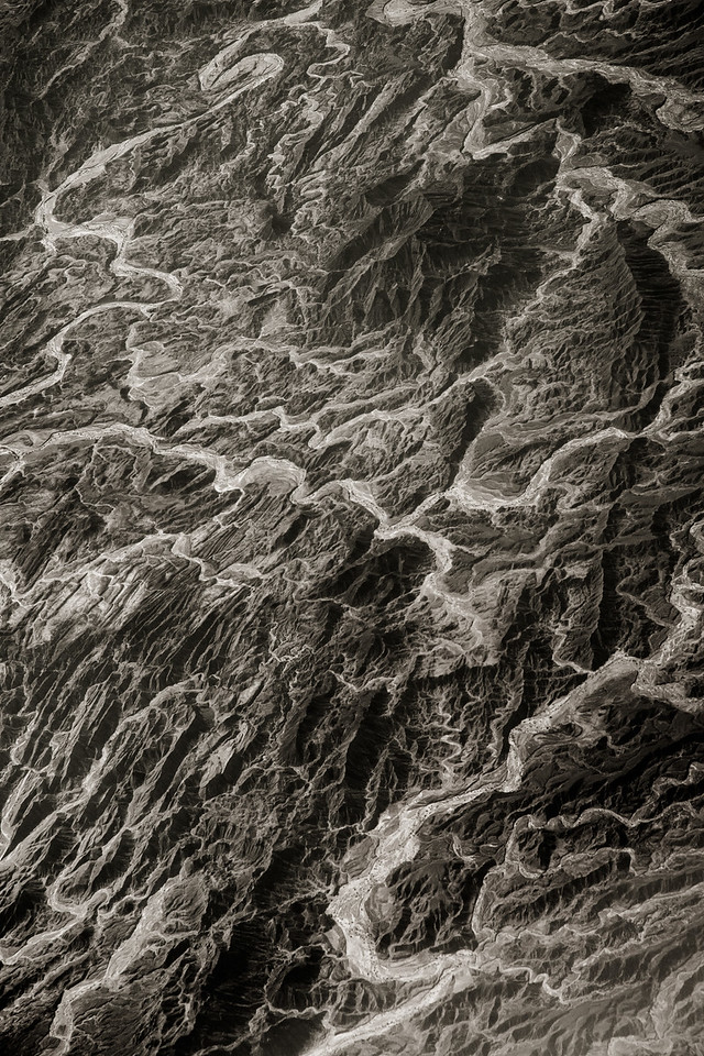 View from plane of Mountains of South West Pakistan. Exposed layers of an anticline, ancient folded rock formed by mountain building process. Rivers winding across exposed rock. Awaran Tehsil 25.590077, 64.795213 (Post work to increase contrast and clarity to compensate for atmospheric haze).