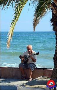 Grk pored mora svira na buzuki