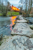 Tarr Steps at dusk in early Spring.  As evening falls, lights come on in the Tarr Steps Inn