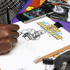 Artist Frankie Washington from Rhode Island works on a drawing at his booth at the Plastic City Comic Con on Saturday in Leominster at the Veterans Memorial Center on West Street. Next to him at his booth is author Jessica Metcalf also from RI. SENTINEL & ENTERPRISE/JOHN LOVE
