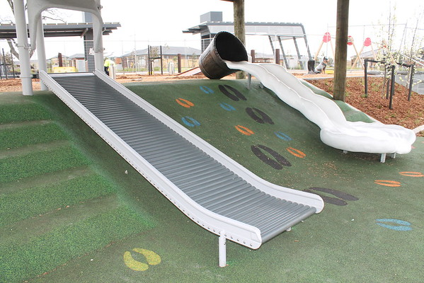roller slide and milk churn slide on artificial turf mound