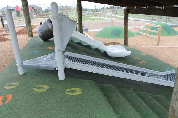 roller slide and milk churn slide on artificial turf mound