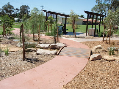 timber bridge in concrete path with sandstone boulders and post and rail shade structures over bbq area
