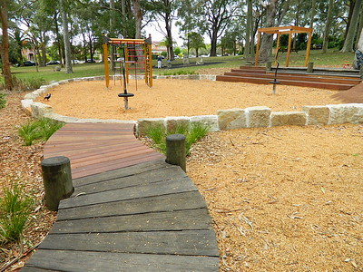 curved raised timber pathway with round posts and sandstone block retaining wall and spinners and timber seating steps and open cubby and climbing frame with cargo net