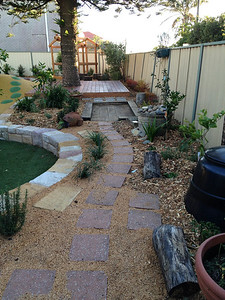 stepping stone path through garden with amphitheatre sitting wall and timber deck