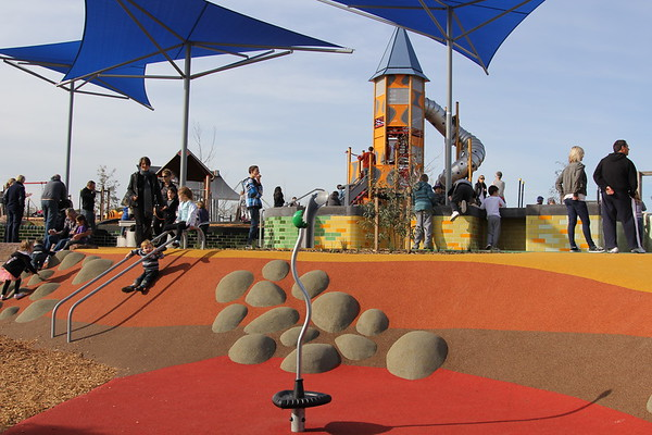 spinner in multi coloured rubber softfall with moulded boulder clambering embankment and parallel slide rails and blue shade structures and raised sandpit and tall rocket slide