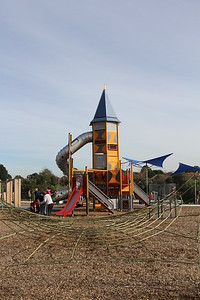 climbing net on softfall mulch and tall fort tower with slide and spiral slide and blue shade structure