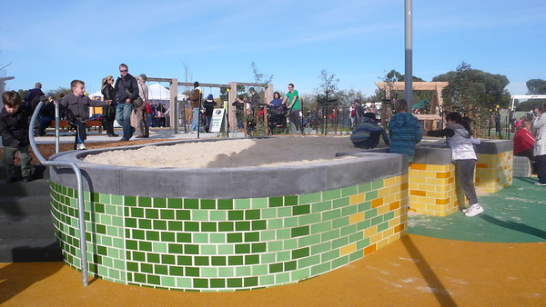 elevated sandpit with accessible bays and green , yellow and orange bricks
