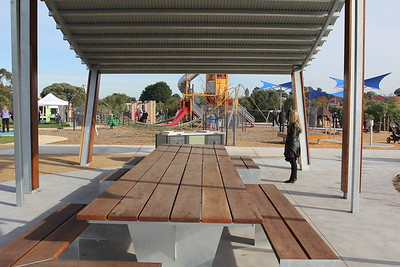 bbq and timber and steel table and benches on concrete with steel shade structure