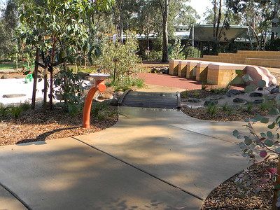 orange water fountain and timber bridge