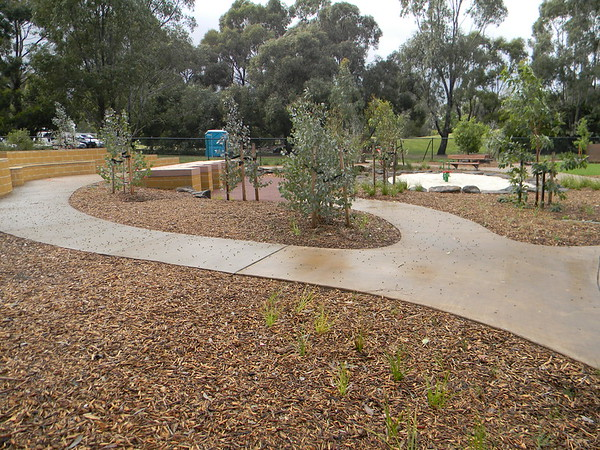 gardens with concrete path and raised sand pit and natural sandpit with boulder edging