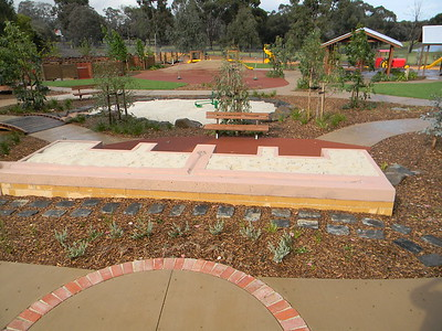 panorama showing raised sandpit bench seat naturalistic sand pit spinners stepping stones and timber bridge