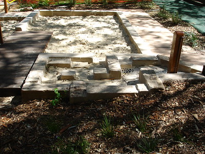 sandpit with sandstone block edging and swale with water play and timber deck