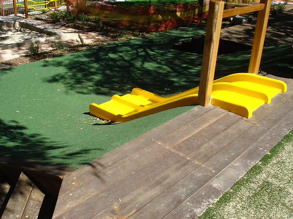 dual yellow plastic slide on embankment