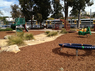 noval spinner and spring rocker in mulch and dry creek bed with grasses and spiral slide and open plan cubby
