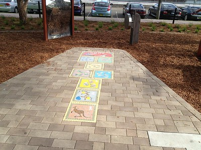 mosaic children's artwork embedded in brick path and distorting mirror and musical wheel