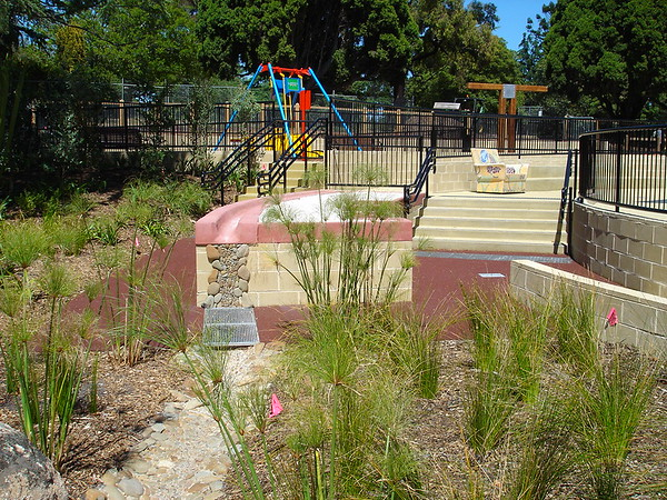 panorama with raised sandpit with mosaic stone edging and chair sculpture and all abilities swing and timber swing