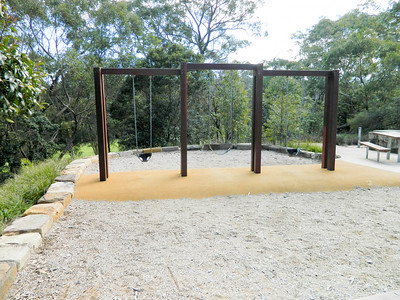 triple timber swing with baby seats on softfall rubber and softfall mulch with sandstone block retaining