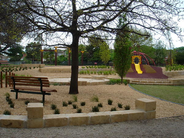 sandstone block edging and bench seat and sandpit and slide on mound