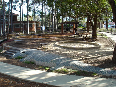 lizard sculpture with inlaid tiles and circular sandpit with sandstone block edging and quad timber swing and gum leaf seats