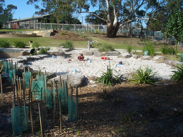 naturalistic sandpit with boulder edges and hand pump for water play