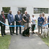 Pleasant Kennels in Leominster held a ribbon cutting on Thursday, July 25, 2019. Manager of the kennels Taryn Lawrence cuts the ribbon during the ribbon cutting. next to her on left is Owner Craig Lemonie and Mayor Dean Mazzarella with members from the North Central Ma Chamber of Commerce and local officals. SENTINEL & ENTERPRISE/JOHN LOVE