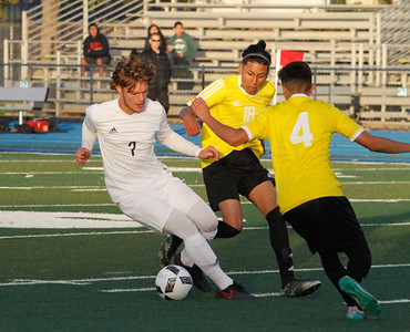 Pleasant Valley's Brad Guymon reaches in to steal the ball away from two Live Oak players in their season opener soccer game Monday November 28, 2016 in Chico, California. (Emily Bertolino -- Enterprise-Record)
