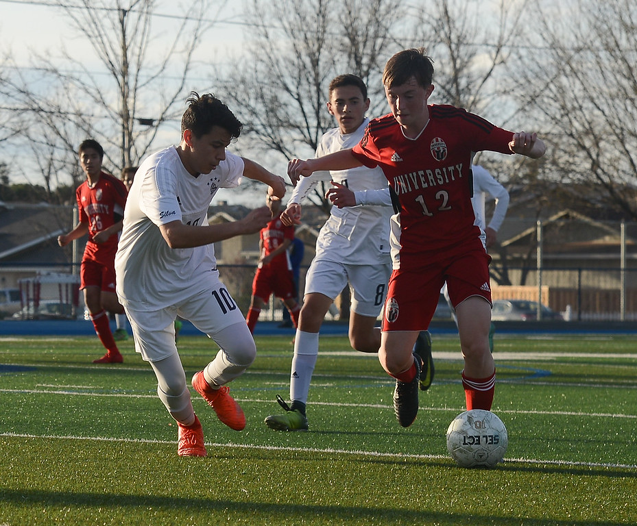 . University High\'s Owen Flanagan (12) dribbles the ball as he\'s defended by Pleasant Valley High\'s Ari Reyes (10), Thursday, March 8, 2018, in Chico, California. (Carin Dorghalli -- Enterprise-Record)