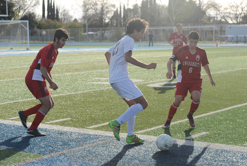 Pleasant Valley High's Tomas Oliveras (23) tries to keep the ball from University High's Kian Chamine (8) and Nico Perry-Mitchell (6), Thursday, March 8, 2018, in Chico, California. (Carin Dorghalli -- Enterprise-Record)